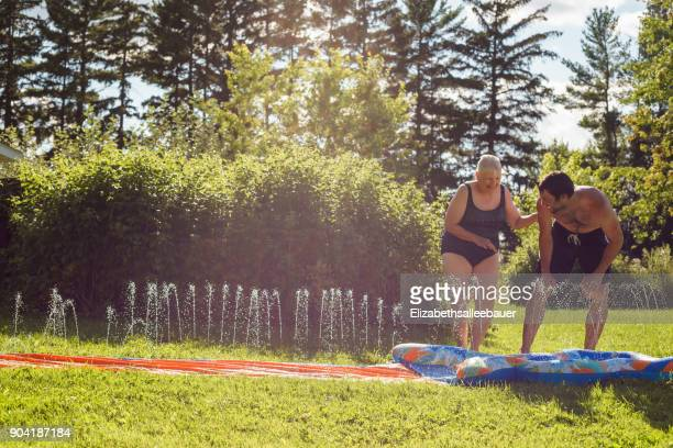 Man and his mother playing on a slip and slide in the garden