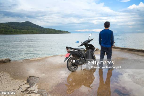 A man and his motorcycle looking into the sea.