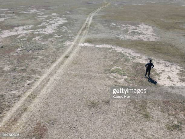 Man and his shadow, standing on arid land