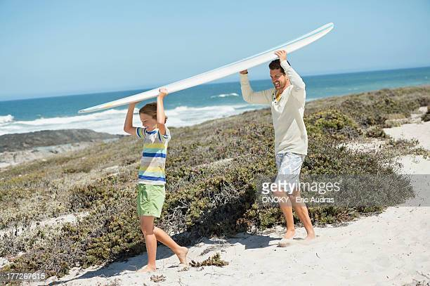 Man and his son carrying a surfboard on the beach