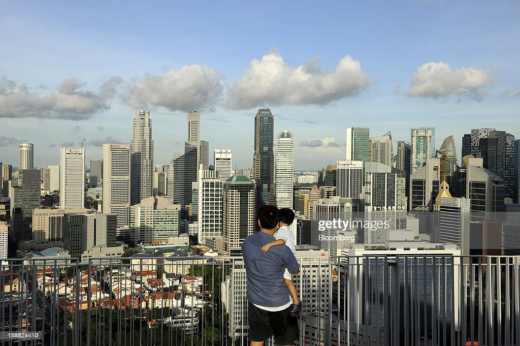 A man and his son look at a view of the central business district in Singapore, on Friday, Dec. 28, 2012. Singapore may grapple with elevated inflationary pressures for a third year in 2013, reducing scope for the central bank to provide stimulus to an economy that probably entered a technical recession this quarter. Photographer: Munshi Ahmed/Bloomberg via Getty Images