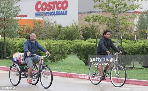 A man and his son pick up supplies on their bicycles from Costco on August 29 2017 in Pearland Texas as the city battles with the aftermath of storm...