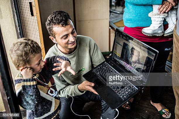 A man and his son talk to a relative in Syria over Skype from the Vrazhdebna reception center in Sofia Bulgaria where over 300 mostly Syrian Kurds...