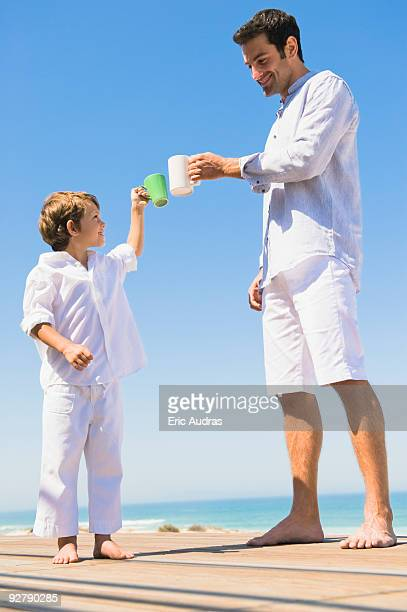 Man and his son toasting with coffee cups on the beach