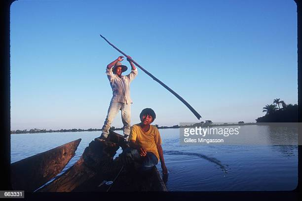 A man and his son travel June 15 1999 on a freshwater lagoon near the Ibare River in the Amazon Basin Bolivia Its varied elevation and climate allows...