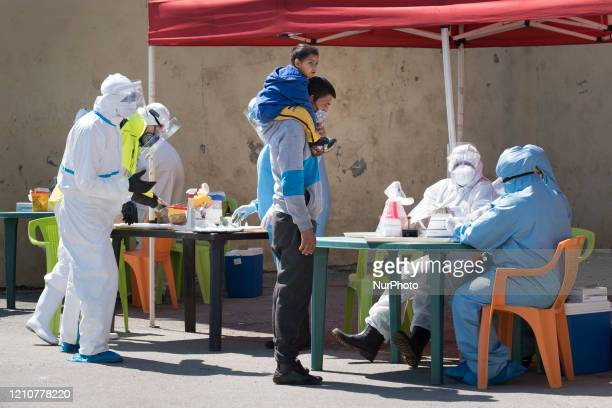 A man and his son waiting to be tested for antibodies or COVID19 at the Roma neighborhood of Fakulteta in Sofia Bulgaria on April 23 2020 Fakulteta...