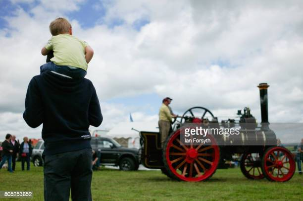 A man and his son watch as a steam engine is driven into the arena during the Duncombe Park Steam Rally on July 1 2017 in Helmsley United Kingdom...