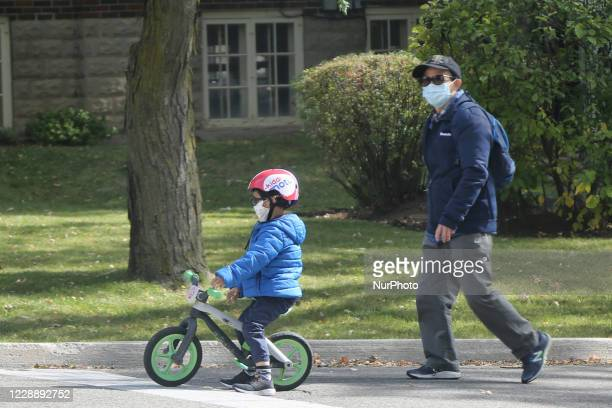 Man and his son wearing face masks to protect them from the novel coronavirus while outside for some exercise during the Autumn season in Markham,...