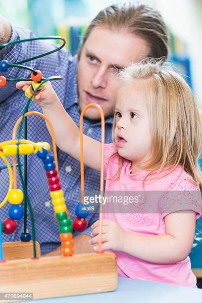 Mann und seine besondere Bedürfnisse Tochter spielt mit Spielzeug