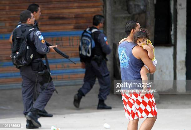 A man and his toddler walk as riot policemen take their positions during the raid in the Morro do Alemao shantytown on November 28 2010 in Rio de...