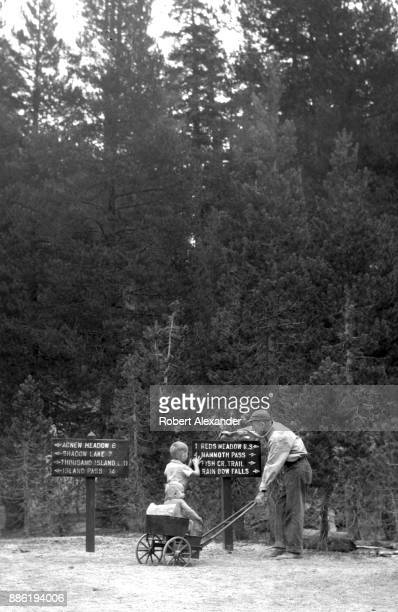 Man and his two sons pause at trail signs at Devil's Postpile National Monument in California's Sierra Nevada mountain range near Mammoth Lakes. The...