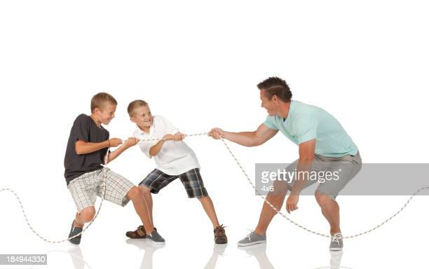 Man and his two sons playing tug-of-war