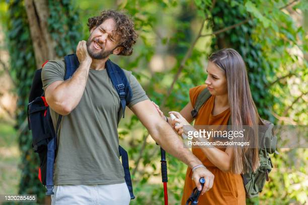man and his wife are scratching itchy skin due to the attack of insects in nature. - insect bites images stock pictures, royalty-free photos & images