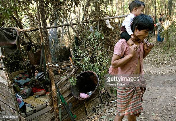 A man and his young child who were forced by the Burmese army to abandon their village walks in front of a hut made from leaves and branches in the...