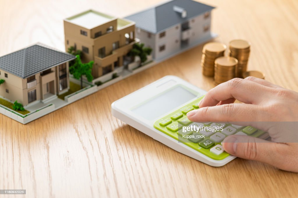 Man and house model calculating with calculator : Stock Photo
