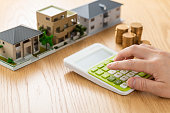 Man and house model calculating with calculator