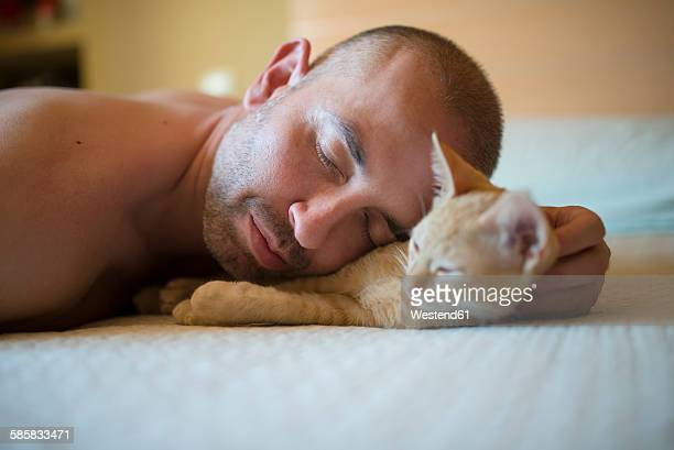 Man and kitten lying on bed, close-up