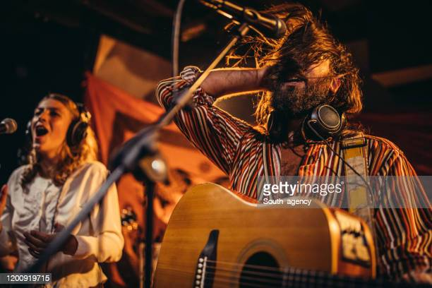 man and lady musicians performing together on stage - acoustic guitar stock pictures, royalty-free photos & images