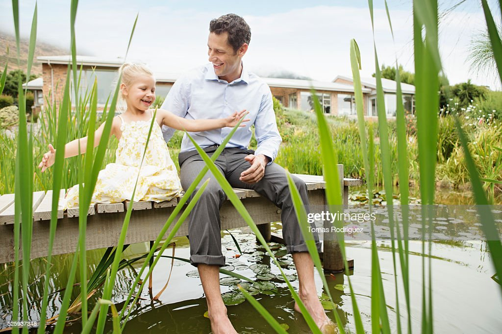Man and little girl (4-5) sitting on jetty : Foto stock