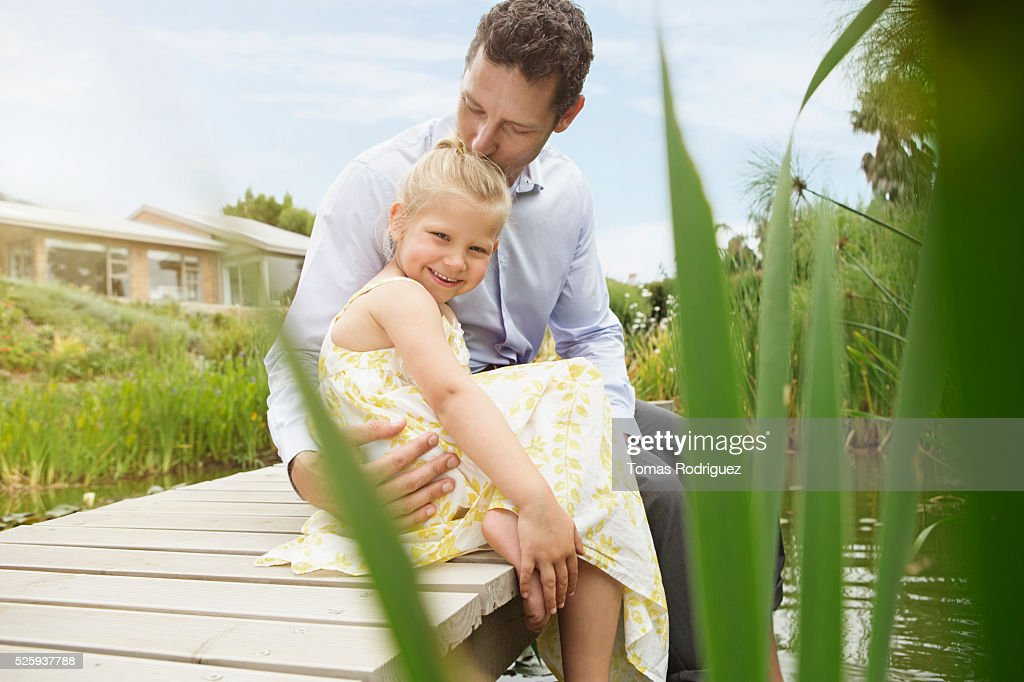 Man and little girl (4-5) sitting on jetty : Stock Photo