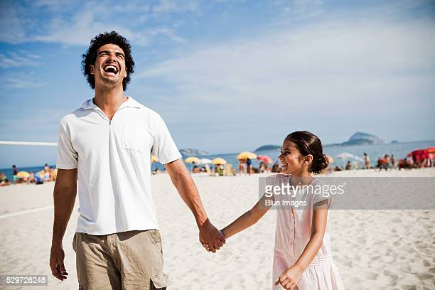 Man and little girl walking on beach