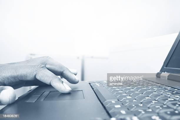 uomo e computer; dita digitando su un computer portatile in monocromatico - l'uomo e la macchina foto e immagini stock
