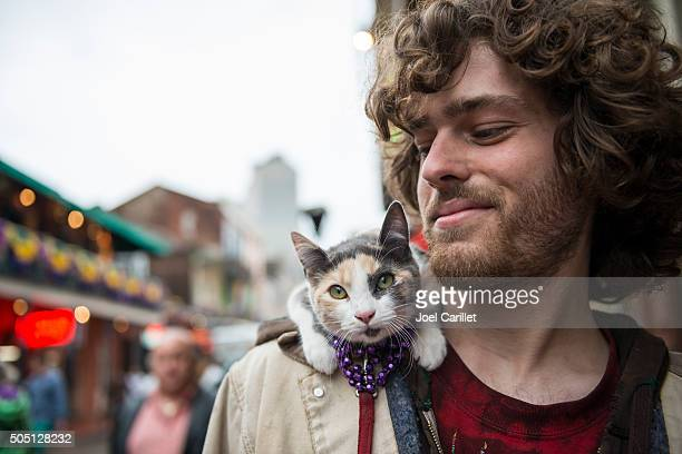 man and pet cat at mardi gras - new orleans - mardi gras party stock photos and pictures