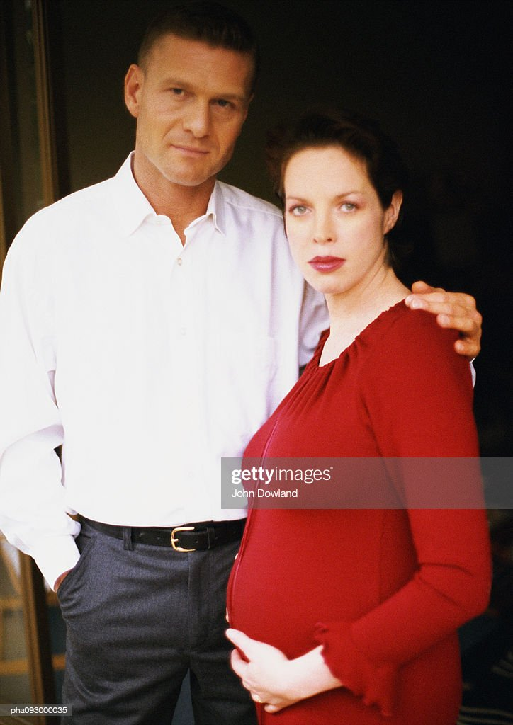 Man and pregnant woman arm in arm, portrait : Stockfoto
