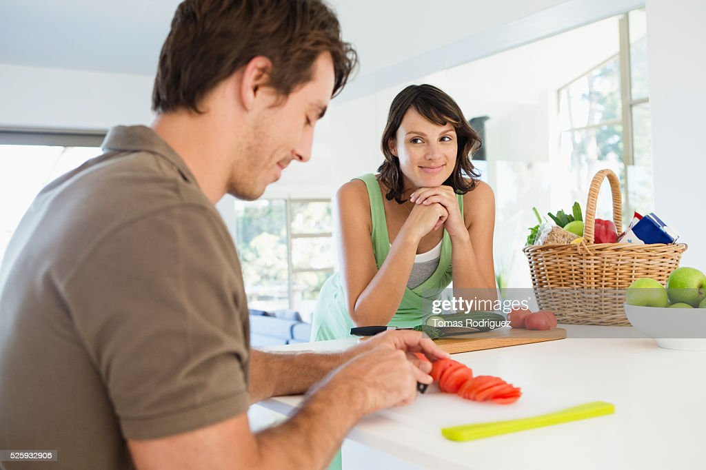 Man and pregnant woman cooking in kitchen : Stock-Foto