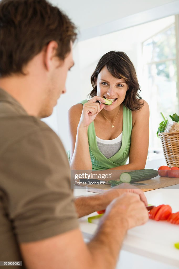 Man and pregnant woman cooking in kitchen : Photo