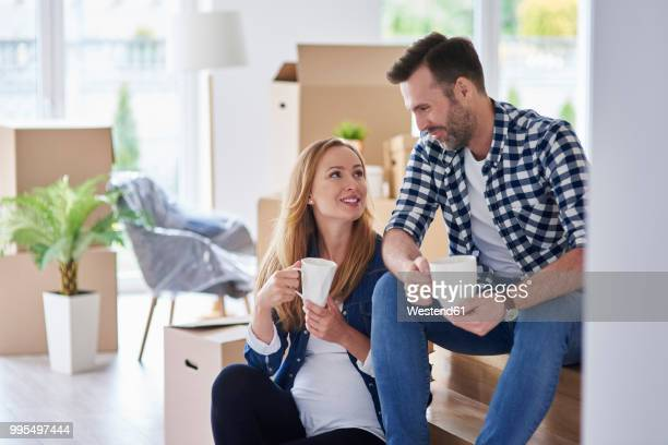 man and pregnant woman moving into new flat having a coffee break - pregnant coffee stock pictures, royalty-free photos & images