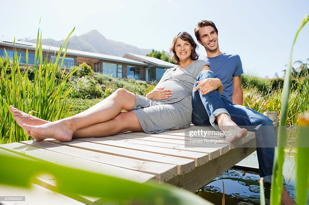 Man and pregnant woman sitting on jetty : Foto de stock