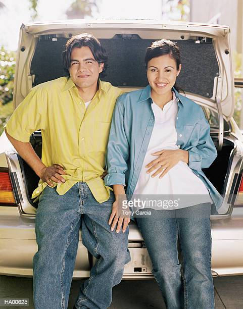 Man and pregnant woman sitting on rear bumper of car, portrait