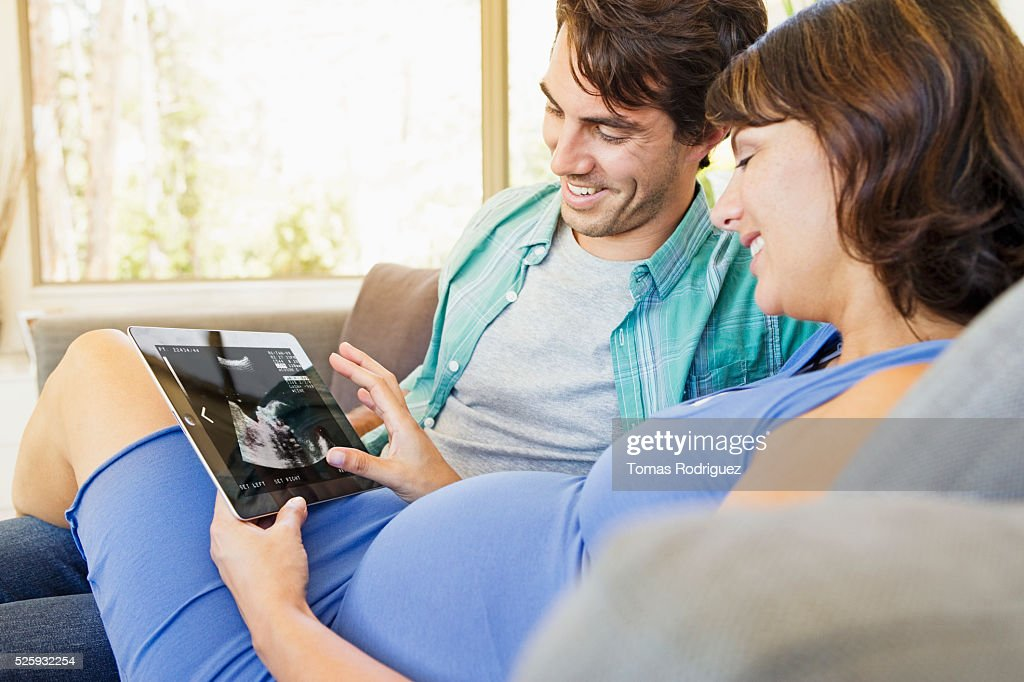 Man and pregnant woman sitting on sofa and using digital tablet : Stock Photo