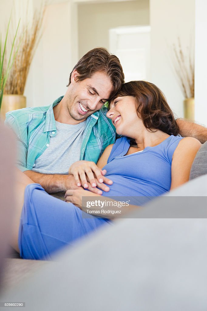Man and pregnant woman sitting on sofa : Stock Photo