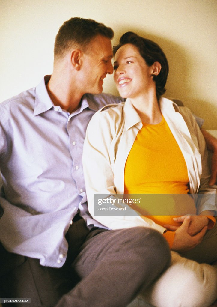 Man and pregnant woman smiling : Stockfoto