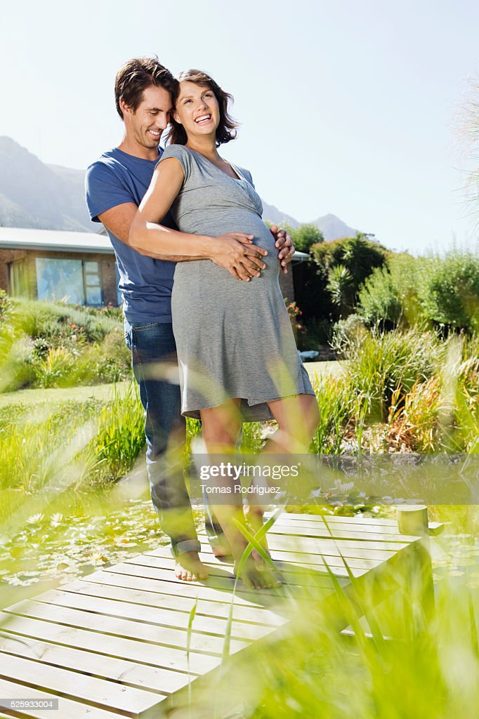 Man and pregnant woman standing on jetty : Stockfoto