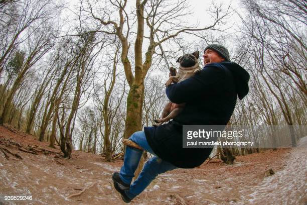 Man and pug on rope swing