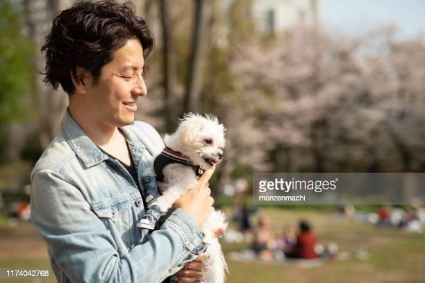 桜の木の下の男と子犬 - 30 34歳 ストックフォトと画像