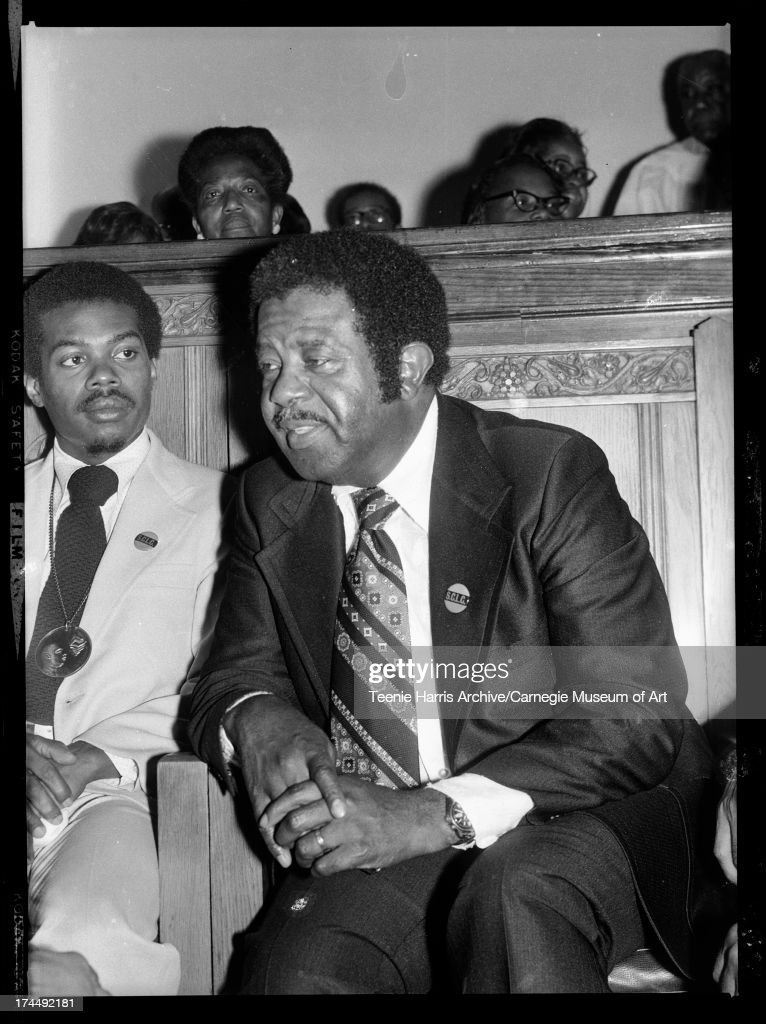 Man and Ralph Abernathy wearing S. C. L. C. buttons, seated on carved wooden bench in Ebenezer Baptist Church, Pittsburgh, Pennsylvania, August 1973.