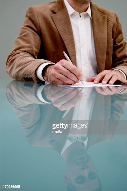 Man and reflection, signing his life away!