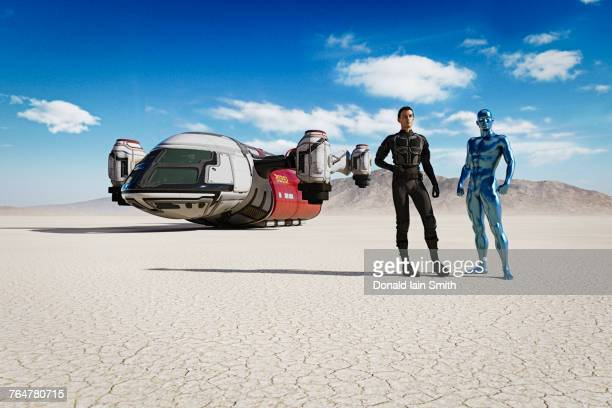 Man and robot in desert with futuristic vehicle