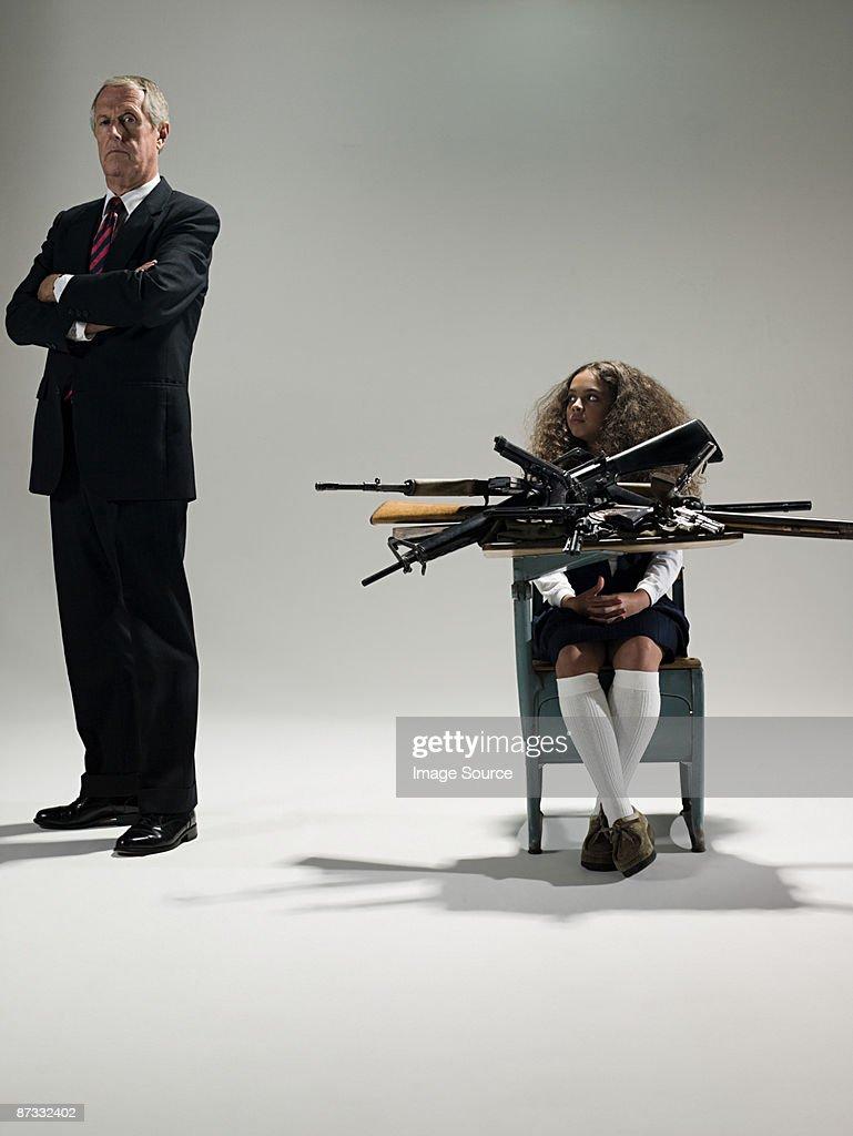 Man and schoolgirl with guns : Bildbanksbilder