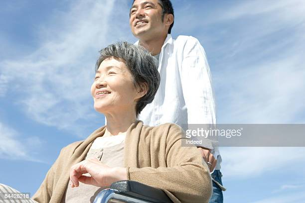 Man and senior woman in wheelchair looking at view