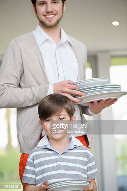 man and son arranging plates for lunch - ボーダーシャツ ストックフォトと画像