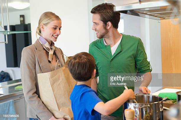 Man and son cooking food for mother returned from shopping