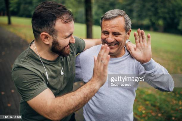 man and son exercising in park together - sportsperson stock pictures, royalty-free photos & images