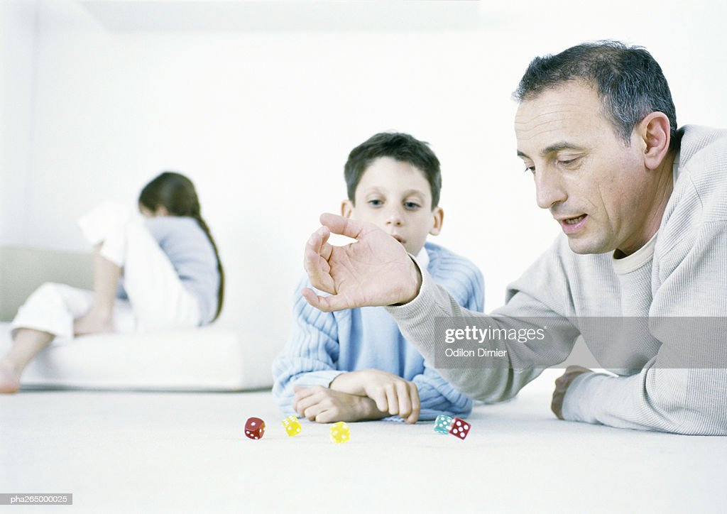 Man and son playing dice on floor, girl sitting in background : Stock Photo