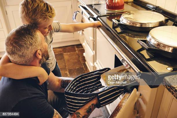 man and son putting vegetables bowl in oven - roast dinner stock pictures, royalty-free photos & images