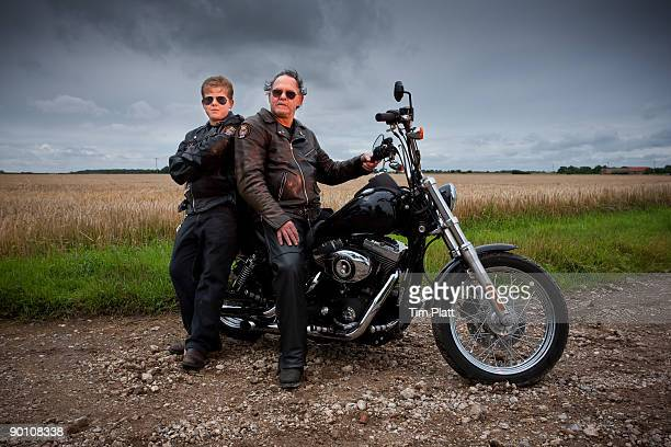Man and son sitting on a motorcycle.